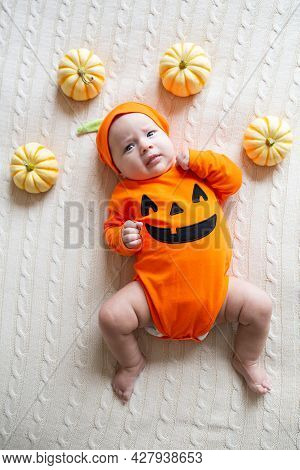 High Angle View Of Baby In Pumpkin Costume. Happy Kid Two Months Old In Orange Halloween Costume On
