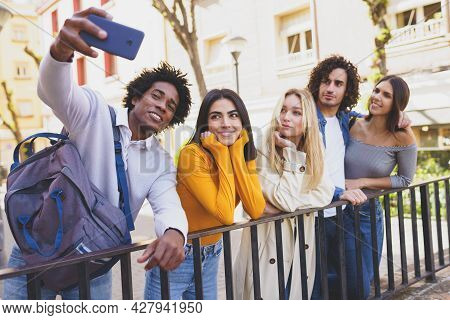 Black Man With Afro Hair Taking A Smartphone Selfie With His Multi-ethnic Group Of Friends.