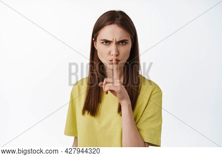 Portrait Of Angry Brunette Girl Shushing, Dont Speak, Keep Quiet Gesture, Hush At Someone With Angry