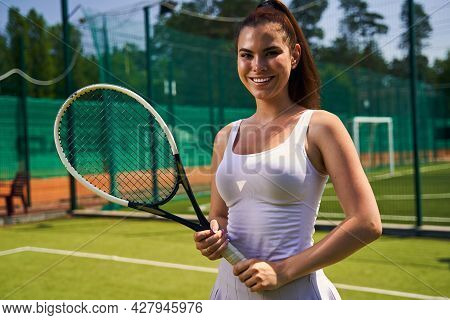 Joyous Sportswoman With A Racket Smiling At The Camera