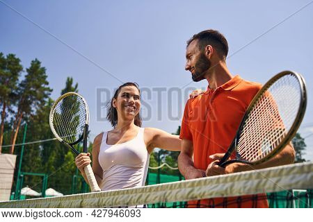 Two Professional Young Athletes With Rackets Gazing At Each Other