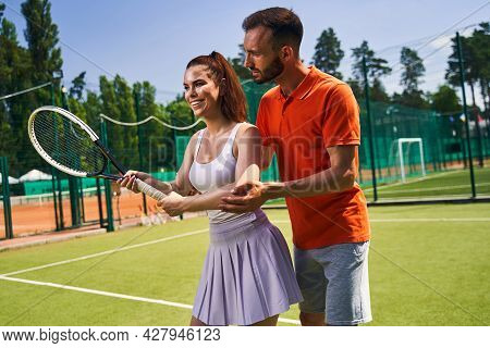 Smiling Beginner Taking A Private Tennis Lesson