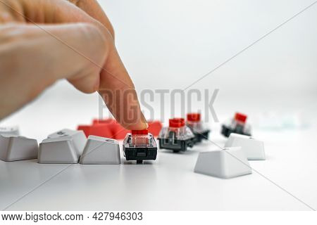 Mechanical Keyboard Switch On A White Background. The Person Presses The Keyboard Switch With His Fi