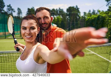 Joyous Attractive Woman Player Being Instructed The Serve Technique