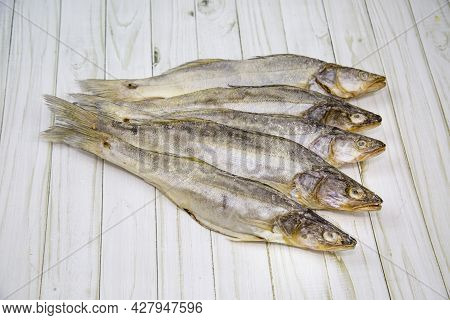 Common Walleye (lat. Sander Lucioperca) Dried With The Head Folded Like A Fan On A Wooden Table. Foo