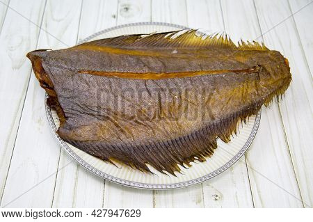 Cold Smoked Halibut Without A Head Is Appetizing On A Round Plate With A Wooden Table Background. Fo