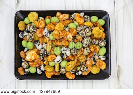 Japanese Mix Or Sea Stones Of Bright Multicolored Colors On A Black Rectangular Plate With A Wooden