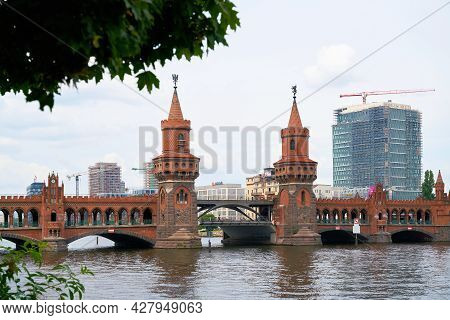 Berlin, Germany - July 16, 2021: The Oberbaum Bridge Over The River Spree In Berlin Connects The Dis