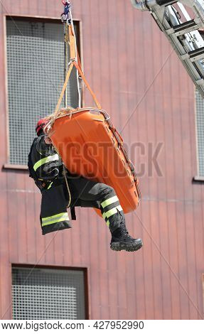 Orange Stretcher With The Injured Person Being Recovered By The Firefighter With An Aerial Platform