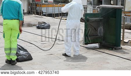 Disinfestation Of Street Furniture During The Coronavirus Epidemic With The Worker In Protective Whi