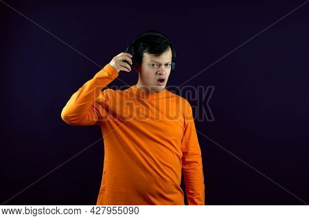 Portrait Of A Man Distracted From Listening To Music. A Man With A Dissatisfied Expression Listens T