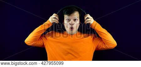 A Man With Headphones Listens To Music With A Surprised Look. A Guy With A Shocked And Surprised Fac