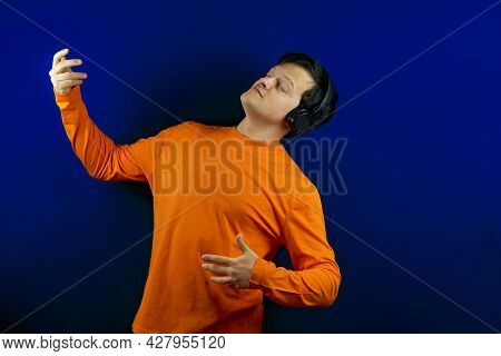 A Man In Headphones Listens To Music And Imagines That He Is Playing The Guitar. The Guy Listens To