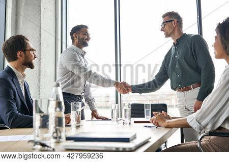 Two Happy Diverse Professional Business Men Executive Leaders Shaking Hands After Successful Financi