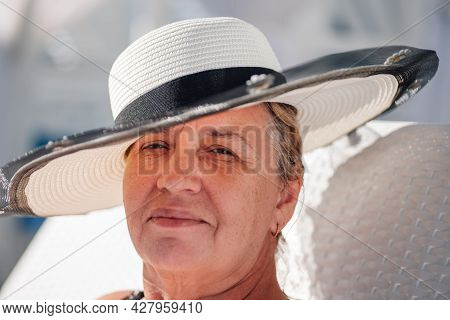 A Woman In A Straw Hat. Close-up Portrait Of An Adult, Smiling Woman In A White Straw Hat On A Brigh