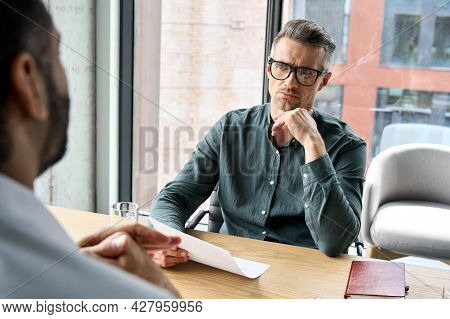 Serious Focused Mature Businessman Employer Hr Or Client Holding Cv Or Contract Listening Manager, A