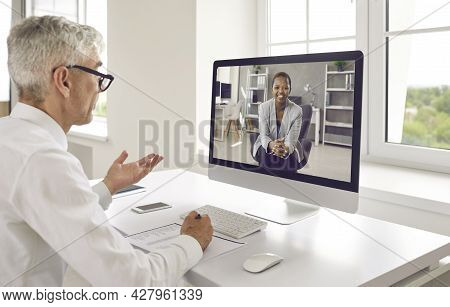 Two Business People Discussing Work In Online Meeting Via Video Call On Computer