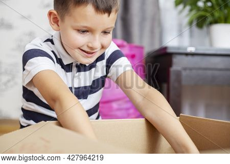 A Boy Is Unpacking Cardboard Box ( Gift Box Or Parcel) At Home. Delivery And Service Concept. Online