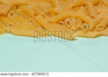 Penne Pasta Background. Pasta Penne Texture Background With Space For Text. Tube Like Macaroni. Heap