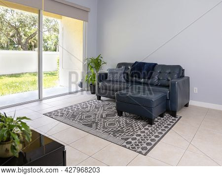 Navy Blue Love Seat And Ottoman By Large Sliding Door.