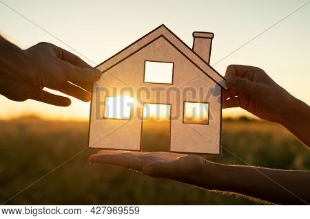 Family Holds Paper House At Sunset, Sun Shines Through Window. Hand Holding Paper Cut Of House Symbo