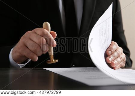 Male Notary Stamping Document At Table, Closeup