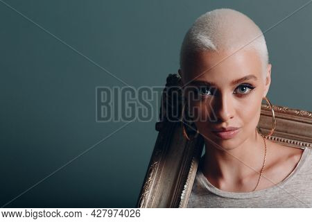 Millenial Young Woman With Short Dying Blonde Silver Hair Holds Gilded Picture Frame In Hands On Her