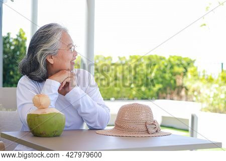 Happy Asian Elderly Woman Wearing White Shirt Sit And Enjoy The Cool Natural Breeze. The Concept Of