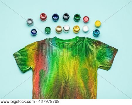 A Large Number Of Cans Of Fabric Dyes And A Tie Dye T-shirt On A Blue Background. Coloring Clothes B