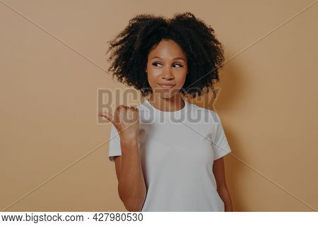 Pretty Curly Haired African Woman Points Thumb Aside, Recommends Promo And Advertises Product With G
