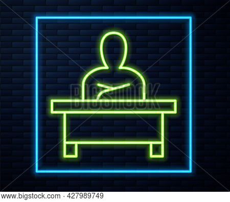 Glowing Neon Line Schoolboy Sitting At Desk Icon Isolated On Brick Wall Background. Vector