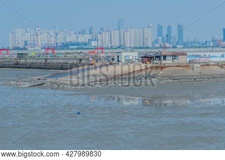 Oido, South Korea; July 23, 2021: Boat Ramp At Oido Port At Low Tide With Highrise Buildings In Back