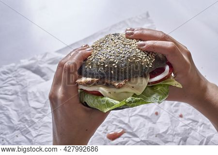 Eating Black Burger. Cropped Shot Of A Person Eating Trendy Black Burger. Delicious Hamburger With B