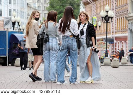 Moscow, Russia - July 2021: Four Stylish Girls Standing On Arbat Street On Crowd Of People Backgroun