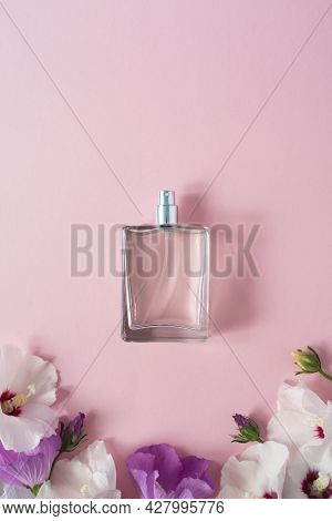 Transparent Bottle Of Perfume With Spray, White And Purple Hibiscus Flowers On A Pink Background. Cl
