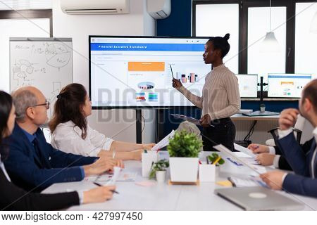 African Leader Briefing Business Organization Pointing At Graph Briefing Teamwork. Corporate Staff D