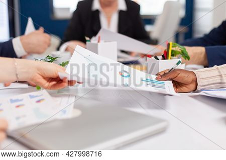 Confident Company Manager Giving Working Tasks To Diverse Teamworkers Analysing Paperwork With Graph