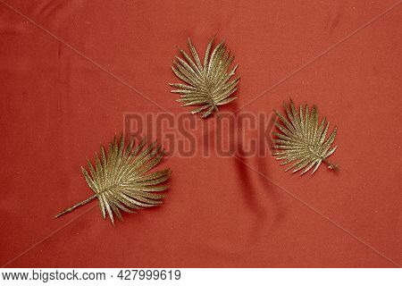 Decorative Golden Leaves On Red Textile Backdrop. Bright, Glamour Autumnal Concept With Fake Fall Le
