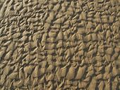 Patterns in the sand left by the receding tide and waves poster