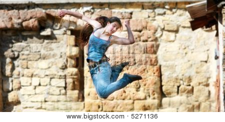 Jumping Girl In Action Over Grunge Background