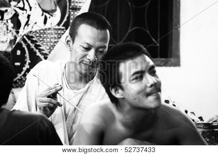 NAKHON CHAI, THAILAND - MAR 23: Unidentified monk makes traditional Yantra tattooing during Wai Kroo Master Day Ceremony (black and white series) on Mar 23, 2013 in Nakhon Chai, Thailand.
