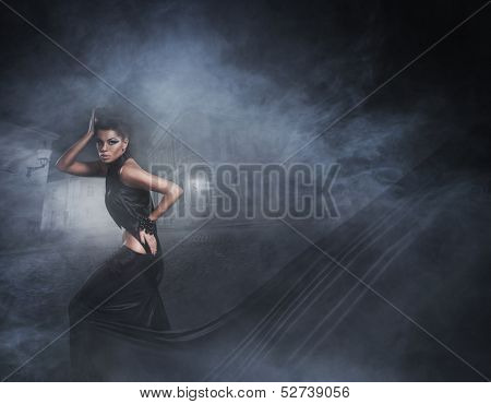 Halloween concept with the young sexy witch running down the street in a black long dress