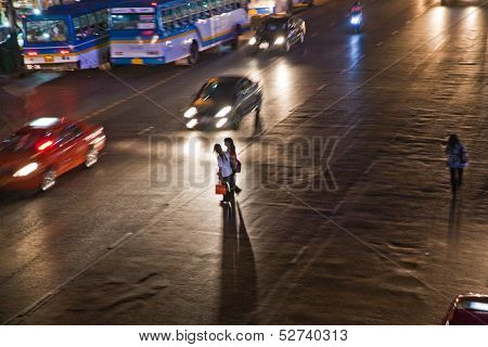 Women Crossing A Mainroad In Bangkok By Night
