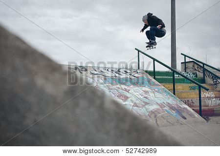 Skateboarder Doing A Ollie Over The Rail In A Skatepark