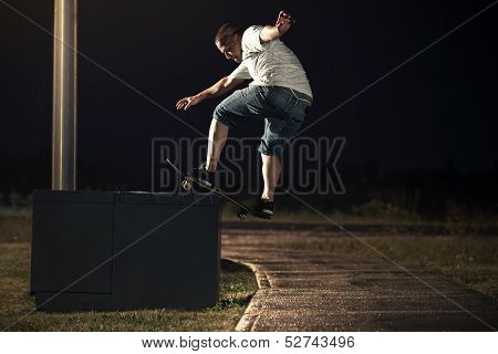 Skateboarder Doing A Frontside Boardslide Trick At Night