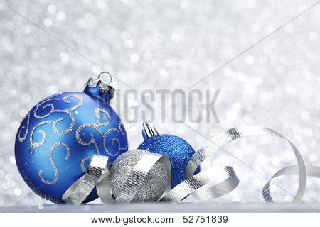 Blue shiny christmas ball on silver glitter background