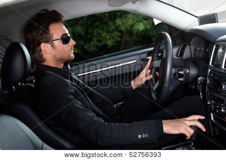 Elegant man driving a luxury car.