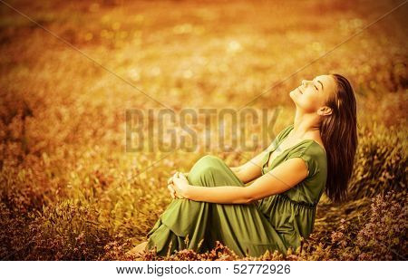 Romantic woman wearing long elegant dress sitting on golden dry field, autumn season, relaxation in countryside, enjoying nature, pleasure concept