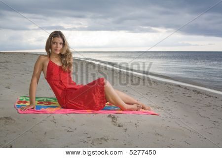 Attractive Girl Sitting On A Towel, With Red Dress