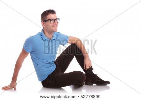 full length photo of a young casual man sitting on the floor and smiling away from the camera. on white background